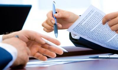 Two sets of hands holding papers and pens